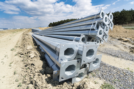 Stack of metal pipes at manufacturing plant construction site. Road construction light posts