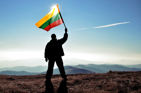 Successful silhouette man winner waving Lithuania flag on top of the mountain peak Фото со стока