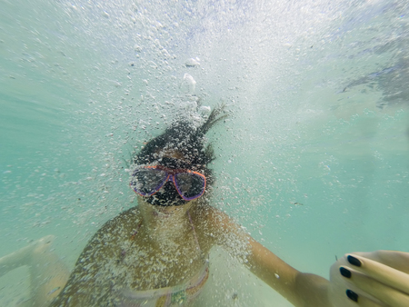 Girl with snorkeling mask makes bubbles and posing the camera Stock Photo