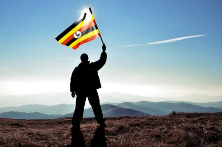 winner man: Successful silhouette man winner waving Uganda flag on top of the mountain peak Stock Photo