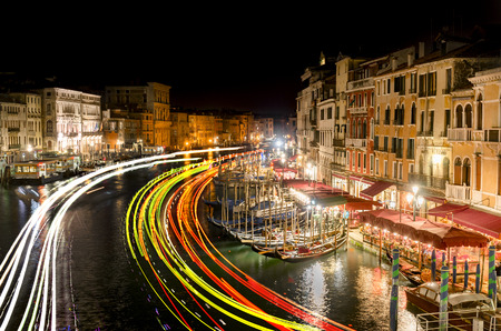 a nocturne: famous grand canale from Rialto Bridge at night with light trails, Venice, Italy