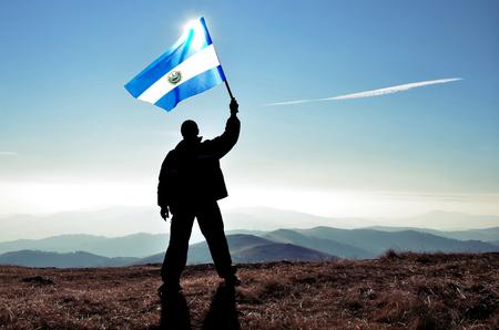 bandera de el salvador: Exitoso hombre silueta ganador agitando El Salvador bandera en la cima de la montaña pico