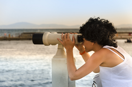 tibidabo: Hipster young girl looking on observation deck, tourist traveler on background panoramic view of the city, coin operated binoculars Stock Photo