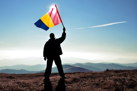 Successful silhouette man winner waving Chad flag on top of the mountain peak