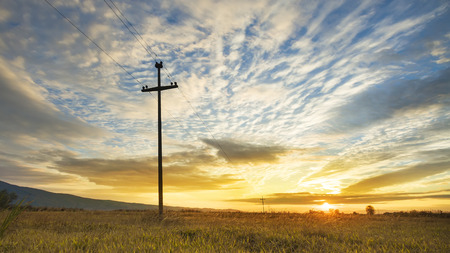 telephone poles: Electricity pole and harvest field on colorful sky, sunset Stock Photo