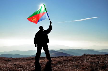 winner man: Successful silhouette man winner waving Eritrea flag on top of the mountain peak