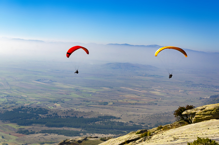 Paragliding flight with blue sky and misty valley