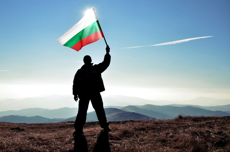 Successful silhouette man winner waving Bulgarian flag on top of the mountain peak