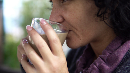 Closeup shot of adult woman relaxing at outdoors drinking a cup of coffee