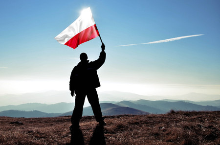 Successful silhouette man winner waving Poland flag on top of the mountain peak