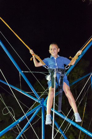 young boy having fun on rope jumping at reverse bungee trampoline at night