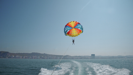 Excited tourists parasailing high in the sky, extreme sport, summer activities