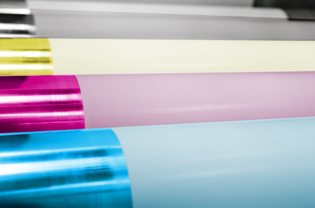 Polygraphic process in a modern printing house with CMYK rollers and roll print paper