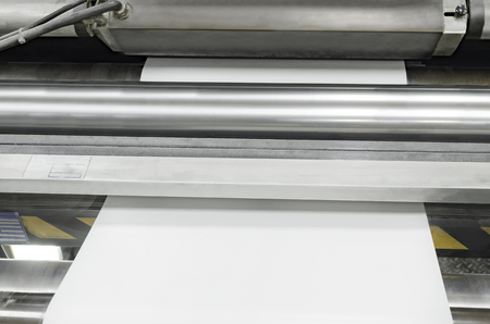 Polygraphic process and white paper and rollers on large print machine  in a modern printing house Stock Photo
