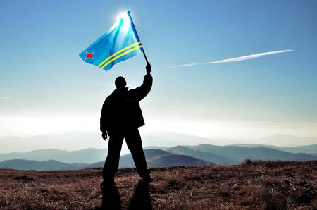 Successful silhouette man winner waving Aruba flag on top of the mountain peak