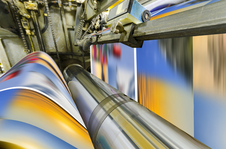 A large offset printing press running a long roll off paper over its rollers at high speed