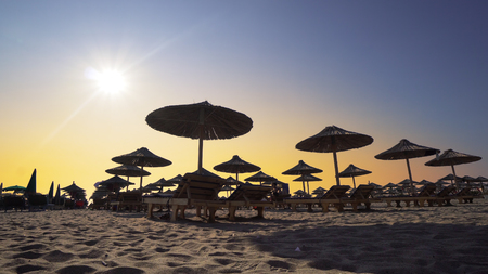 Beach chairs with umbrella on the beach at sunset. Cinematic steadicam shot Stock Photo