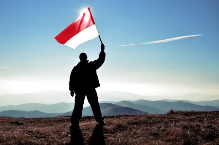 Successful silhouette man winner waving Monaco flag on top of the mountain peak