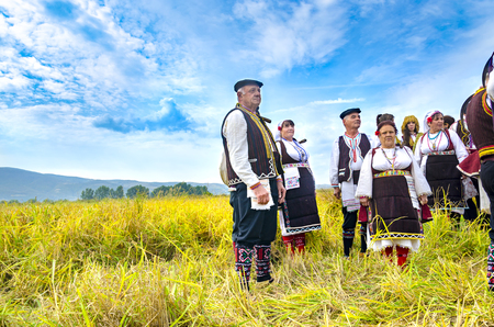 Kochani, Macedonia - circa Jun, 2015: People dressed in old ethno clothes at manual rice harvesting manifestation on sunny day Editorial