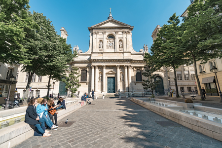 Paris, France- circa May, 2017: People are reading books while sitting beside the water fountains of Place de la Sorbonne in front of Eglise de la Sorbonne on a summer afternoon.