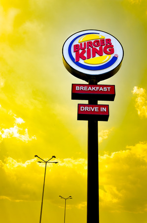 Burger King Drive in road sign sunrise orange sky at the restaurant located on highway