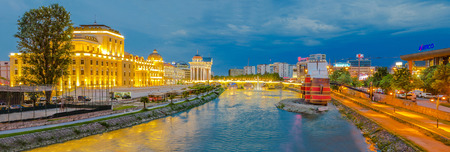 View on Stone bridge and National Theater illuminated in Skopje in the evening
