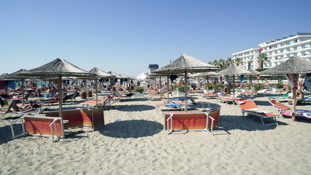 View of nice tropical sandy beach with umbrellas and beach beds in Durres, Albania, cinematic steadicam shot 報道画像