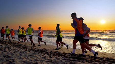The soccer team, coaching training running outdoor under the beach sunset, cinematic steadicam shot