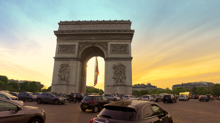 Tourist POV on street crossing with view of beautiful sunset over Arc de Triomphe. Paris, France