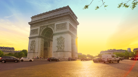 Traffic drives along Arc de Triomphe circle at Sunset. It is one of the most famous monuments in Paris. Redakční