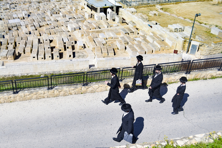 Jewish people in traditional suit at the Mount of Olives Jewish Cemetery