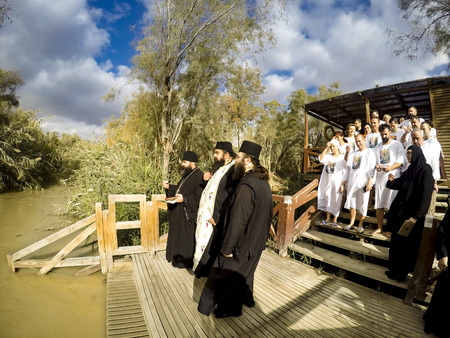 Religious christians with white clothes going into the water of the Jordan river at baptismal site Qasr el Yahud near Yericho