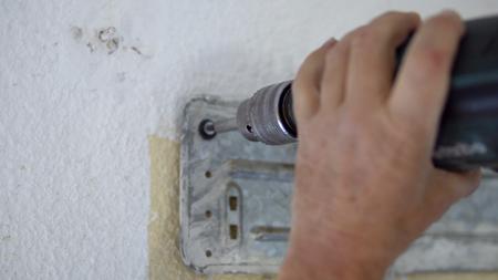 Electric screwdriver tighten screws on air conditioner indoor unit during instalation