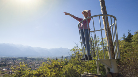 Young girl at forest navigation, observation point above town pointing with hand Imagens