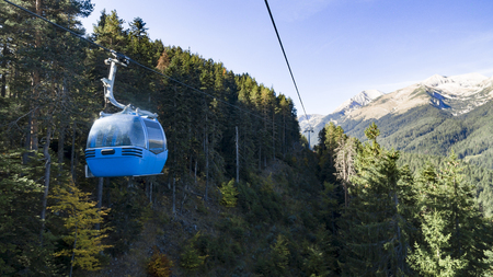 Gondola ski lift against mountain forest and summit