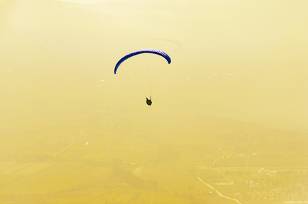 Paraglider flies on background of sunset sky