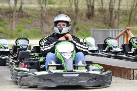 Young Man adjust helmet on Go-Kart Car on A Playground Racing Track - Go Kart Is A Popular Leisure Motor Sports Stock Photo