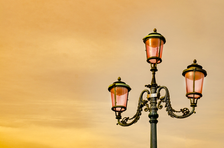 lantern street lights of San Marcos square against sunset orange sky, in Venice, Italy