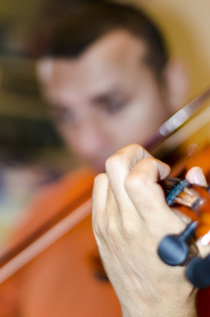 Male musician playing violin on dark background