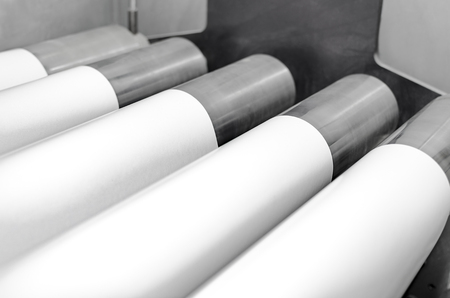 Polygraphic process and white paper and rollers on large print machine  in a modern printing house Imagens