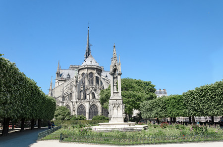 Exterior of Notre-Dame de Paris with Notre Dame Fountain Of The Virgin Statue in garden, Paris, France