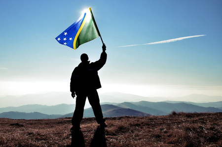 Successful silhouette man winner waving Solomon Islands flag on top of the mountain peak Stock Photo