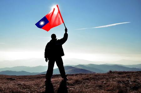 Successful silhouette man winner waving Taiwan flag on top of the mountain peak