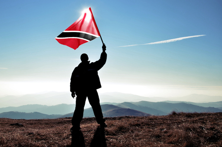 Successful silhouette man winner waving Trinidad and Tobago flag on top of the mountain peak