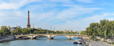 Panoramic view of Paris with bridge Pont des Invalides, Seine river and Eiffel Tower at background on spring sunny day