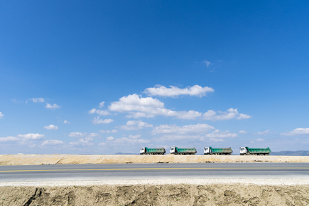 Road construction site with four trucks against blue sky Stock Photo