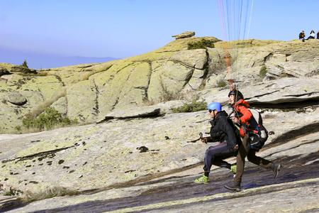 Biplace de parapente décollant de falaise de montagne Banque d'images