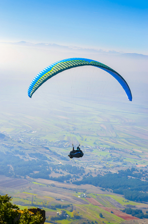 Paraglider over valley, aerial pov