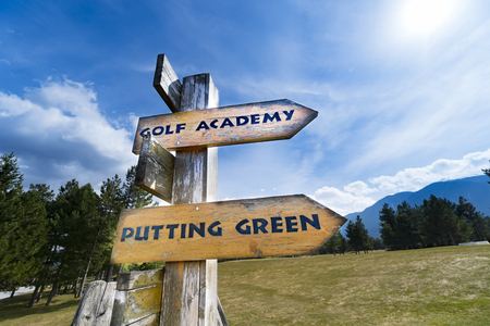 Signpost with golf course information on the wooden sign arrows. Stock Photo