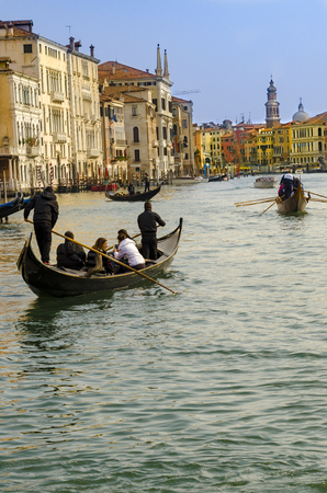 VENICE, ITALY - circa MARCH, 2016: Grand Canal with gondolier and tourists on tour in Venice, Italy